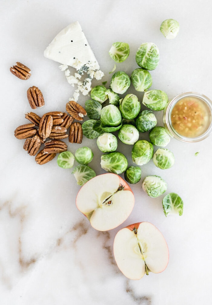 overhead view of brussels sprouts, pecans, blue cheese, apples, and bacon dressing on a white marble background.