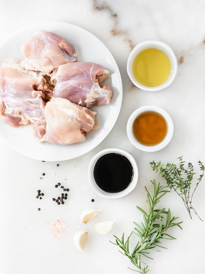 overhead view of ingredients needed to make maple thyme grilled chicken thighs on a white marble background.