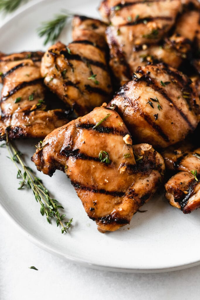 closeup of maple thyme grilled chicken thighs on a plate with thyme and rosemary sprigs.