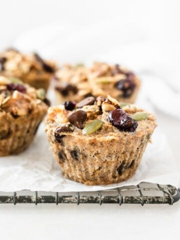 trail mix baked oatmeal muffins on a wire cooling rack lined with parchment.
