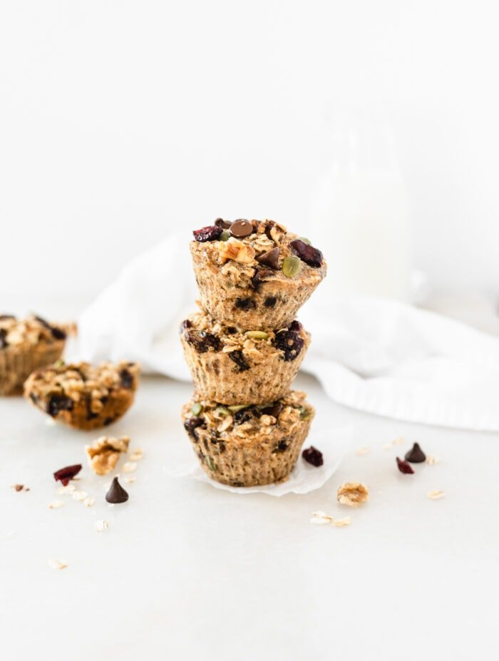 three trail mix baked oatmeal muffins stacked on top of each other.